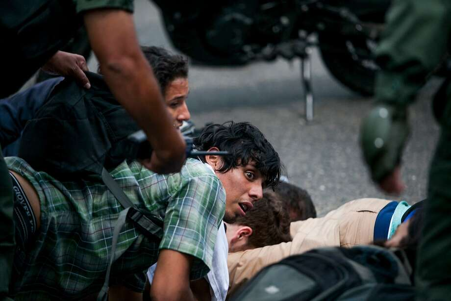 An anti-government demonstrator is held on the ground along with others, as he is detained by the Bolivarian National Guard, during clashes at a protest in Caracas, Venezuela, Wednesday, May 14, 2014. Members of Venezuela's opposition pulled out of crisis negotiations with the government as security forces arrested scores of people in fierce clashes with demonstrators. (AP Photo/Alejandro Cegarra) Photo: Alejandro Cegarra, Associated Press