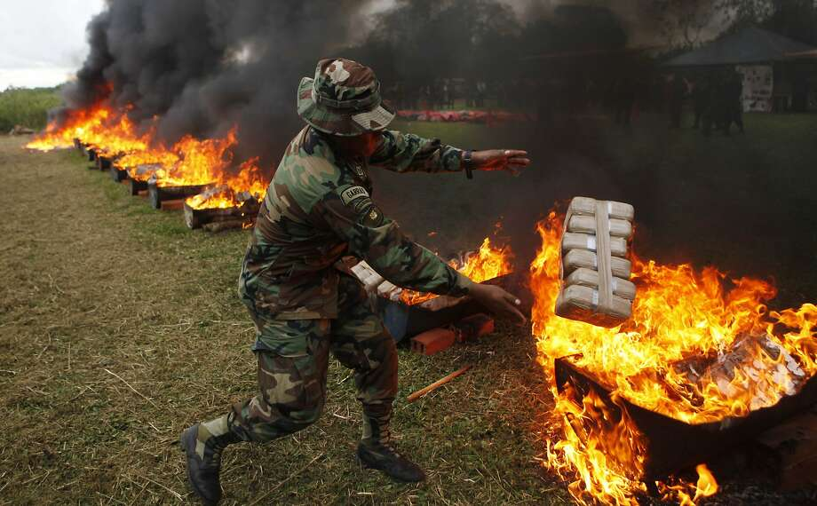 Anti-narcotics police agents incinerate seized packages of cocaine, in Trinidad, Bolivia, Wednesday, May 14, 2014. Anti-drug police burned over 1500 kilograms of drugs seized during last week's operations on the eastern region Beni, according to Police Colonel Mario Centellas, director of Bolivia's special forces against drug trafficking. (AP Photo/Juan Karita) Photo: Juan Karita, Associated Press