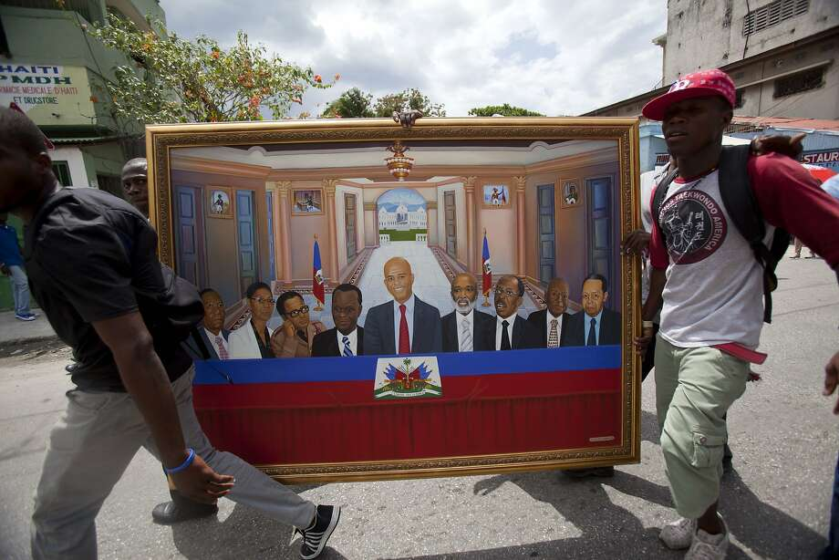 Supporters of Haiti's President Michel Martelly carry a painting where Martelly, center, is flanked by former Haitian presidents during an event to mark his three years in power in Port-au-Prince, Haiti, Wednesday, May 14, 2014. A couple thousand people protested in Haiti's capital as they marked the third anniversary of Michel Martelly's presidency and called for his departure. The protesters tried to reach the area near the National Palace where Martelly was commemorating the anniversary with a street party of his own, but they were turned away by police barricades and riot-control officers who used tear gas to disperse them. ( AP Photo/Dieu Nalio Chery) Photo: Dieu Nalio Chery, Associated Press