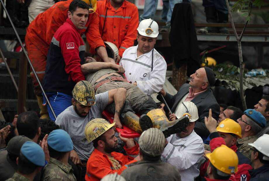 Rescue workers carry a rescued miner from the mine in Soma, western Turkey, early Wednesday, May 14, 2014. Rescuers desperately raced against time to reach more than 200 miners trapped underground Wednesday after an explosion and fire at a coal mine in western Turkey killed at least 205 workers, authorities said, in one of the worst mining disasters in Turkish history. Turkey's Energy Minister Taner Yildiz said 787 people were inside the coal mine in Soma, some 250 kilometers (155 miles) south of Istanbul, at the time of the accident and 363 of them had been rescued so far. (AP Photo/Emrah Gurel) Photo: Emrah Gurel, Associated Press