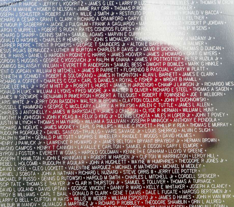 A person looks at some of the more than 58,000 names are on The Wall that Heals, Wednesday, May 14, 2014, in Myrtle Beach, Va. The tribute to Vietnam veterans is located at Grand Park beside The Market Common. It is part of Military Appreciation Days in Myrtle Beach. It's a half-scale replica of the Vietnam Veterans Memorial in Washington, D.C. The wall will be at the site until Sunday. (AP Photo/The Sun News, Janet Blackmon Morgan) LOCAL PRINT OUT (MYRTLE BEACH HERALD OUT, HORRY INDEPENDENT OUT, CAROLINA FOREST CHRONICLE, GEORGETOWN TIMES OUT) Photo: Janet Blackmon Morgan, Associated Press