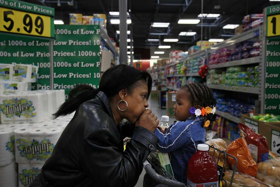 Cassaundra Peoples (l to r) kisses her granddaughter, Zamiyah Gordon-Evans' (right), 2, hands while grocery shopping at Foods Co with Toby Evans (not shown) on Thursday, May 8, 2014 in Oakland, Calif. Evans and Peoples, who are engaged, knew they couldn't use their WIC vouchers at the store as they had asked upon arriving. Photo: Lea Suzuki, The Chronicle