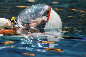 NASA astronauts Stan Love is lowered in to the water to conduct a test run of the MACES spacesuit in the Neutral Buoyancy Lab at the Johnson Space Center on Friday,  May 9, 2014, in Houston.   Modified versions of the orange space shuttle launch and entry suits, the spacesuits are being developed for spacewalks on an asteroid exploration mission planned for the the 2020s.