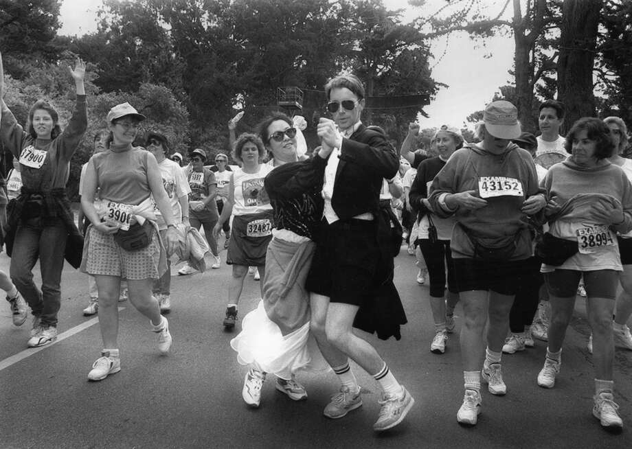Rich Maloney and Karen Sue from San Mateo dance their way through crowds while enjoying the 1994 Bay to Breakers.  Photo: Lea Suzuki, SFC