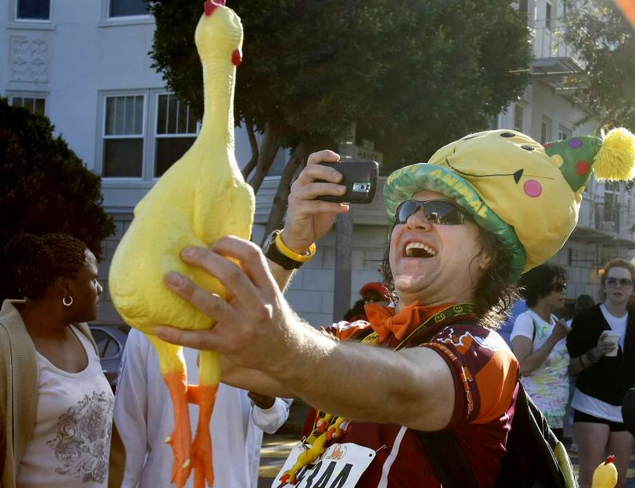 Hans Bernhardt got a shot of one of his many rubber chickens he wore during the 98th running of the Bay to Breakers. Photo: Brant Ward, The Chronicle