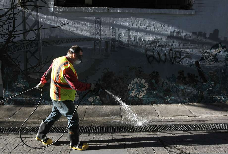 Steve Mahoney of the S.F. Department of Public Works sprays disinfectant on the ground before using a power washer to clean Jack Kerouac Alley in May. Photo: Paul Chinn, The Chronicle
