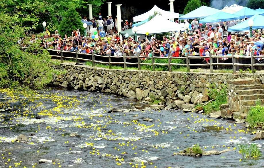 Spectators watch as 4,000 plastic ducks float in the waters of the Pootatuck River in Sandy Hook during the Newtown Lions Club's Great Pootatuck Duck Race. This year the annual event will be Saturday, May 24. Photo: Michael Duffy, ST / The News-Times