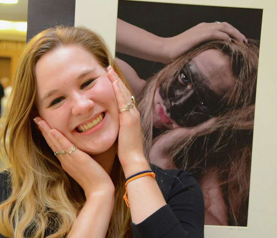 "Life imitating art?  Lizzie Crigler has some fun with Charlotte Burch's portrait of her, at the opening of ""unchARTed,"" the 27th Annual Senior Art Show, at New Canaan High School, Wednesday evening, May 14, 2014. Photo: Jeanna Petersen Shepard, Freelance Photo / New Canaan News freelance"