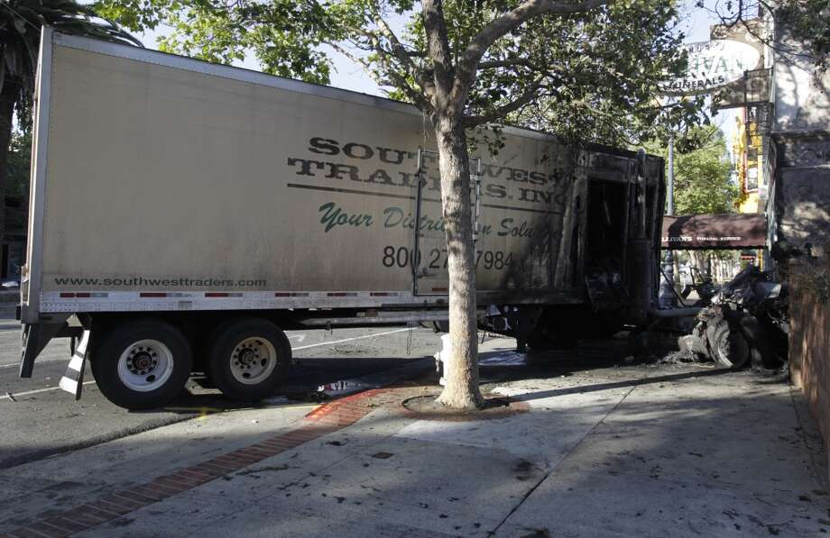 Charred remnants of a big rig remain in place after the driver apparently lost control and slammed into a wall of Sullivan's Funeral Home on Market Street between Sanchez and Noe streets in San Francisco, Calif. on Thursday, May 15, 2014. A hazmat crew was called in to remove fluids from the truck before it could be towed. Westbound Market Street remained closed to traffic well into the morning. Photo: Paul Chinn, The Chronicle