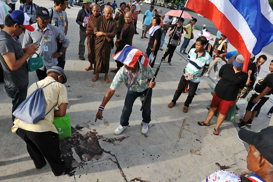 BANGKOK, THAILAND - MAY 15: Protesters and bystanders examine the scene of a deadly drive-by attack on an anti-government rally site at the landmark Democracy Monument on May 15, 2014 in Bangkok, Thailand. Unidentified assailants on a pick-up truck attacked the protest site overnight with a grenade and gunfire, killing two protesters and wounding over 20. The attack came amid fears of violence between rival pro and anti-government groups in Thailand's ongoing political turmoil. (Photo by Rufus Cox/Getty Images) Photo: Rufus Cox, Getty Images