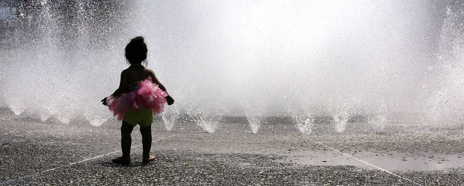 Tutu hot: A young ballerina contemplates cooling off in the water jets of the Salmon Street 