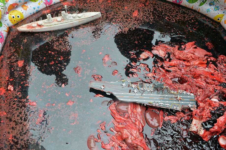 Wading pool of gore:Toy ships float in animal blood and guts from an abattoir during a demonstration outside the French embassy in Kiev. Activists of Ukrainian Democratic Alliance organization used the bloody display to protest France's sale of two Mistral-class helicopter carriers to Russia. Photo: Sergei Supinsky, AFP/Getty Images