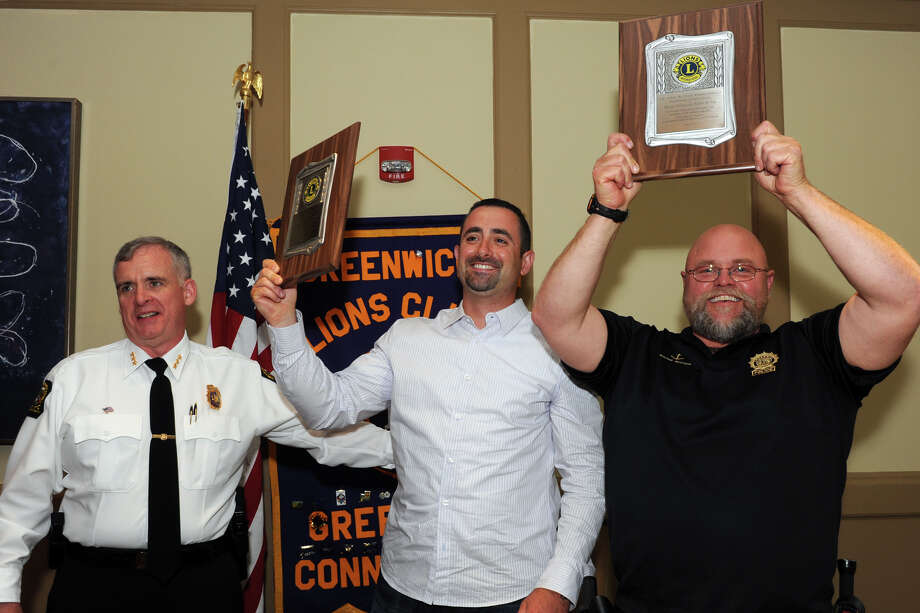 Greenwich Police Chief James Heavey, left, presented the Greenwich Lions Club's annual John A. Clarke Memorial Award to Officers Francesco DiPietro, center, and Shawn Fox during a luncheon in Greenwich, Conn. May 15. 2014. Photo: Ned Gerard / Connecticut Post