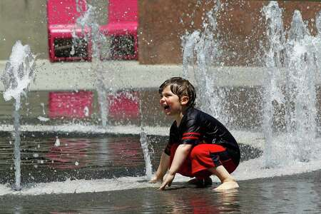 Thijs Talluto, 3, of Los Angeles, plays in a fountain at Grand Park in downtown Los Angeles Monday, May, 12, 2014. A warm weekend gave way to a sweltering work week in Southern California, with whipping winds of the sort already felt across the West bringing dry conditions and high fire danger. After a hot, windy Mother's Day with temperatures in the mid-80s, a high pressure system was expected to heighten the heat slightly Monday before pushing it to near triple digits in some spots midweek, mostly inland areas already badly parched by drought. High temperatures will extend up and down California, according to the National Weather Service.