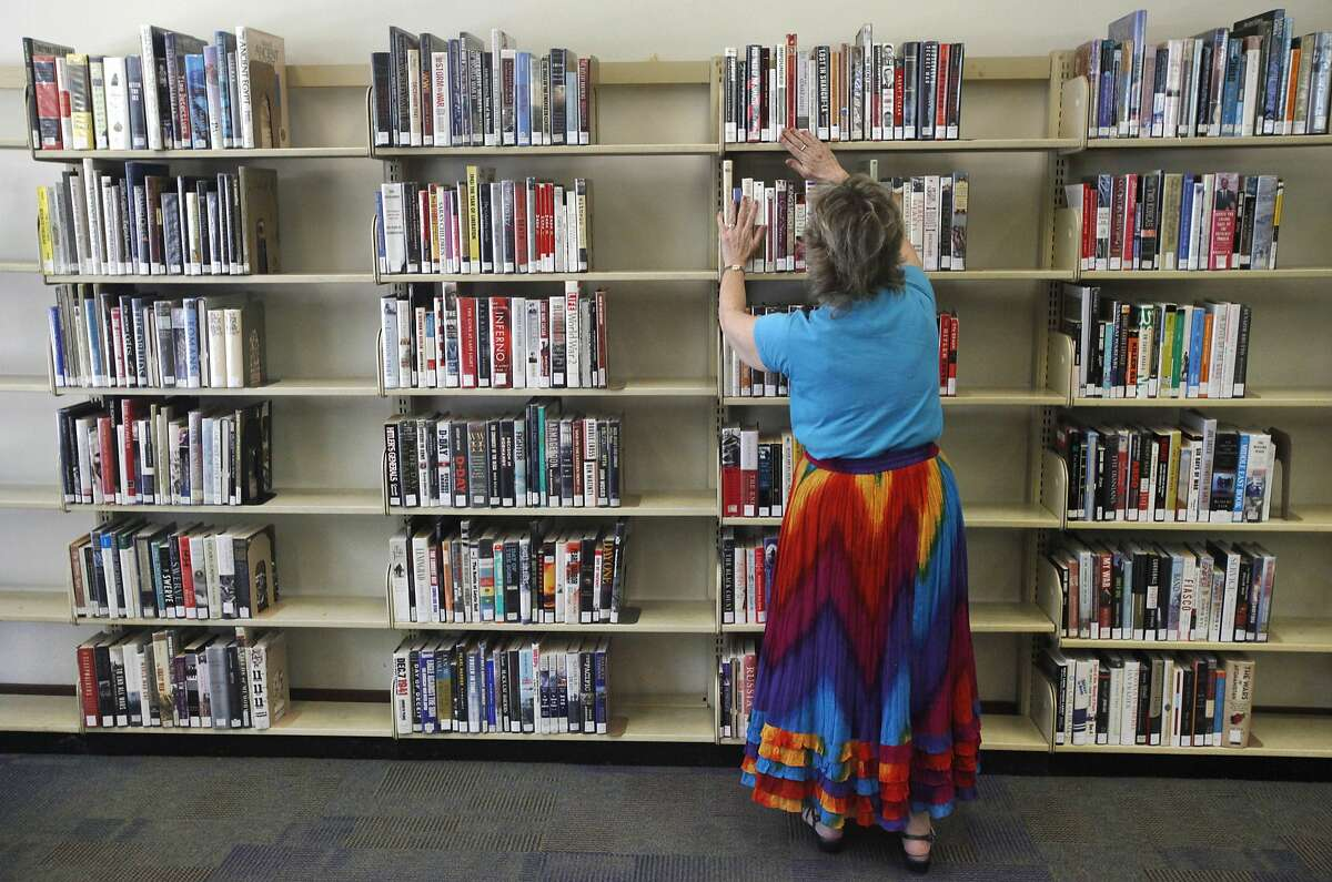 Adult Services Librarian Heidi Ontiveros checks that books are in the proper order, known as