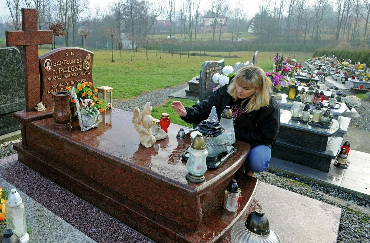 Anna Palosz lights a candle on the grave of her son Bart, at the cemetery in Kalna, Poland, Friday, Nov. 22, 2013.