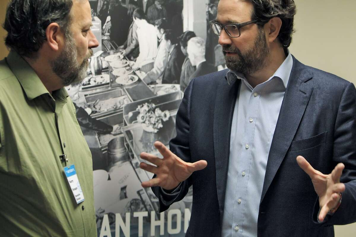 Mikkel Svane, the CEO of Zen Desk, speaks with Barry Stenger, Executive Director of the St. Anthony Foundation after Svane presented St. Anthony's Clinic with a check for $141,000, on Friday, February 7, 2014, in San Francisco, Calif. ZenDesk featured St. Anthony's on their website as one of 3 organizations to be the beneficiary of $25 from new customer starter plans. The donation on Friday comes from donations for the past 6 months.
