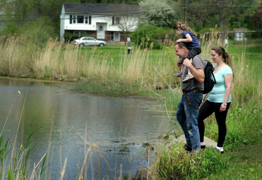 Paul and Alycia Matchen of Bethel, Conn., and their daughter, Rachelle, 3, walk near the pond at Meckauer Park in Bethel, Tuesday, may 13, 2014. Photo: Carol Kaliff / The News-Times
