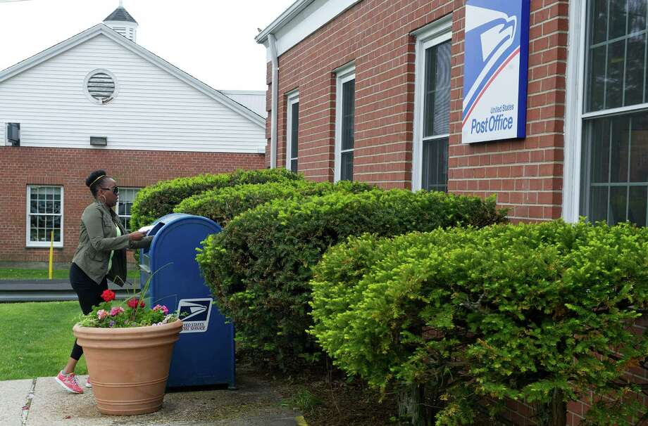 Wendy Spann drops mail at the Post Office on Hope Street in Stamford, Conn., on Thursday, May 15, 2014. Photo: Lindsay Perry / Stamford Advocate