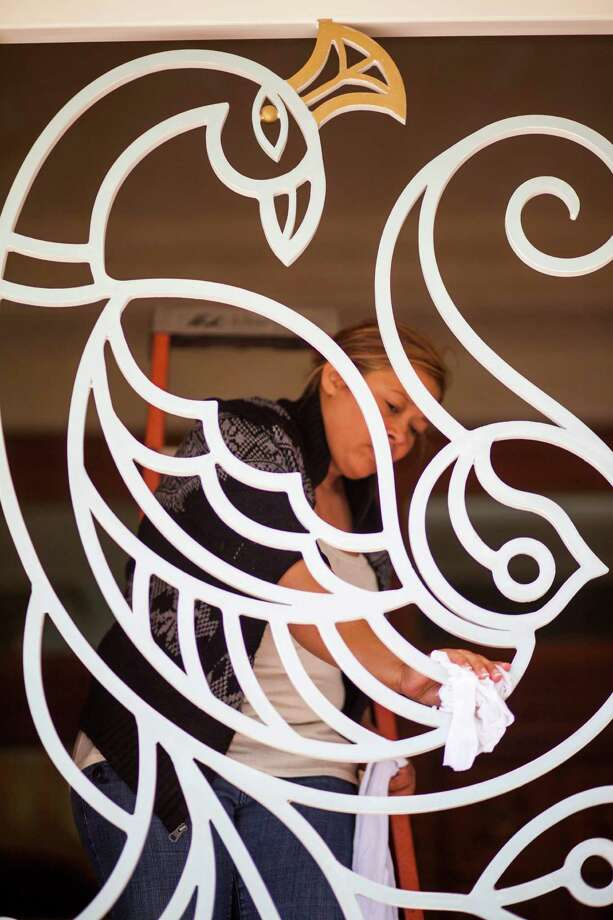 A worker cleans gate designed as a peacock at the Hare Krishna Temple & Cultural Center, May 13, 2014 in Houston. Photo: Eric Kayne, For The Chronicle / Eric Kayne