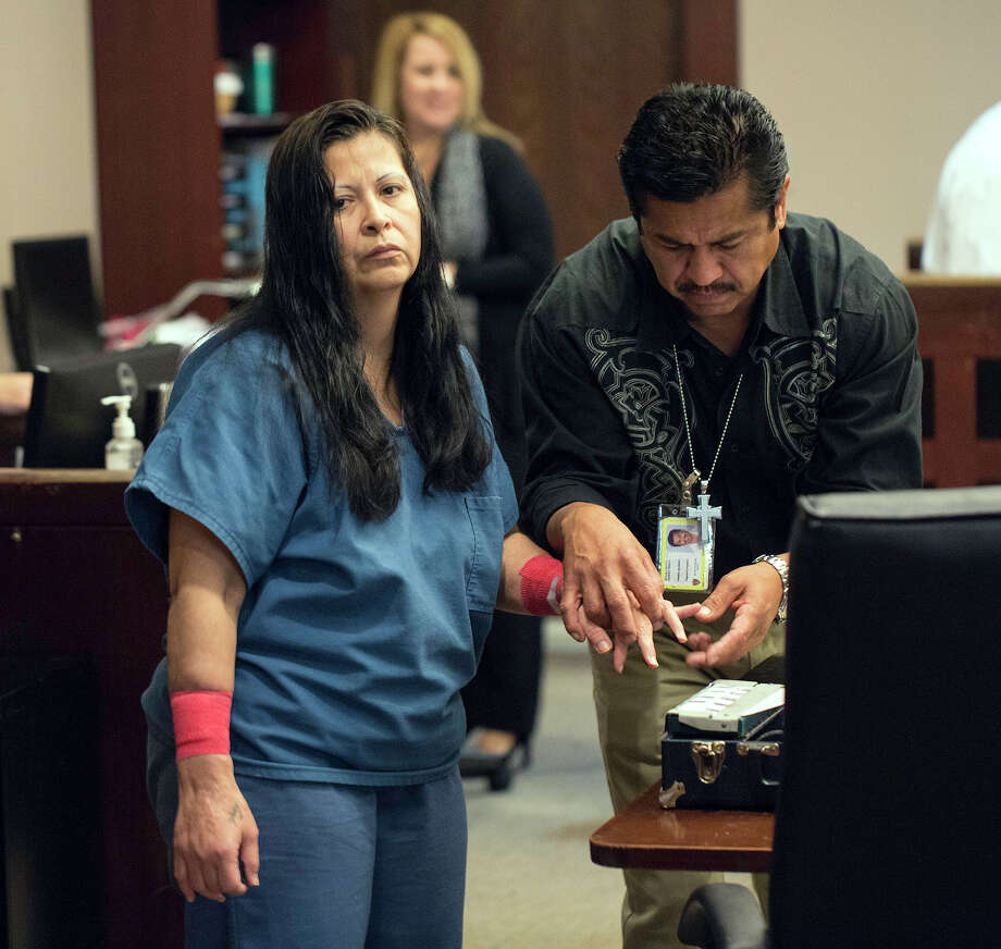Originally convicted in absentia of dragging her dog, Gorda, to death behind a truck, Herlinda Trigo, left, gets finger printed prior to appearing before Judge Pat Priest in the 144th District Court for sentencing, Thursday, May 15, 2014 at the Cadena-Reeves Justice Center in San Antonio. Photo: J. MICHAEL SHORT, FOR THE EXPRESS-NEWS / Photo Copyright ©2014 J. MICHAEL SHORT