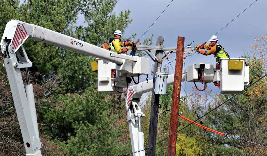 National Grid lineman, Jason Risley, left, and Nate Johnson work to replace a utility pole on Parkis Mills Road in Galway Friday afternoon October 22, 2010. (John Carl D'Annibale / Times Union) Photo: John Carl D'Annibale / 00010730A