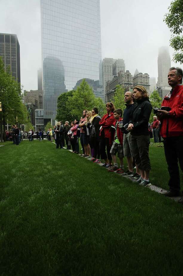 People watch a live video from the Ground Zero memorial site of the dedication ceremony of the National September 11 Memorial Museum on Thursday, May 15, 2014 in New York. Photo: Spencer Platt, Associated Press / POOL Getty Images