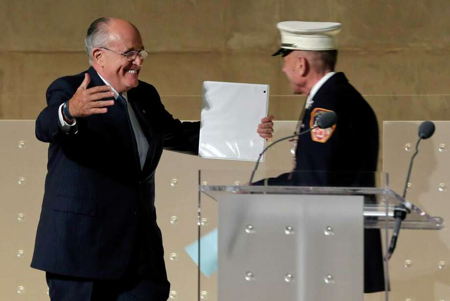 Former New York Mayor Rudolph Giuliani, left, greets New York City firefighter Mickey Kross before his speech during the dedication ceremony in Foundation Hall, of the National September 11 Memorial Museum, in New York, Thursday, May 15, 2014. Photo: Richard Drew, Associated Press / Pool AP