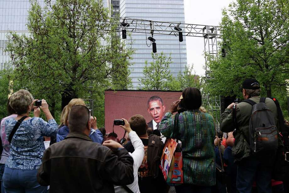 "People watch a live video from the Ground Zero memorial site of President Barack Obama during the dedication ceremony of the National September 11 Memorial Museum in New York on May 15, 2014. The museum spans seven stories, mostly underground, and contains artifacts from the attack on the World Trade Center Towers on September 11, 2001 that include the 80 ft high tridents, the so-called ""Ground Zero Cross,"" the destroyed remains of Company 21's New York Fire Department Engine as well as smaller items such as letter that fell from a hijacked plane and posters of missing  loved ones projected onto the wall of the museum. The museum will open to the public on May 21. Photo: Spencer Platt, Associated Press / Pool Getty Images"