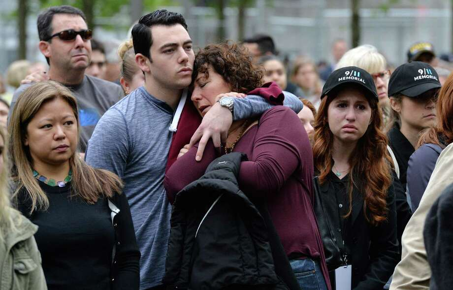 Two people embrace while gathered on the plaza of the National September 11 Memorial to watch the telecast of the dedication ceremony at the National September 11 Memorial Museum in New York on Thursday, May 15, 2014. Photo: JUSTIN LANE, Associated Press / POOL EPA