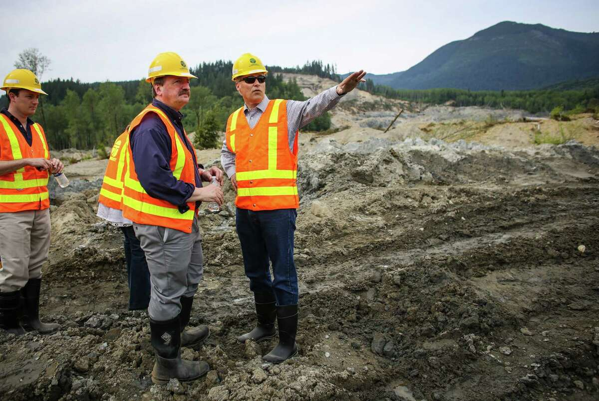 Washington State Governor Jay Inslee speaks with Snohomish County Council Chairman Dave Somers as Inslee checks on progress at the site of the Oso mudslide on Thursday, May 15, 2014 in Oso, Wash. Crews are progressing on unearthing State Highway 530. Some parts of the road will have to be rebuilt after it was washed away in the march mudslide that killed 41 people and left 2 missing.