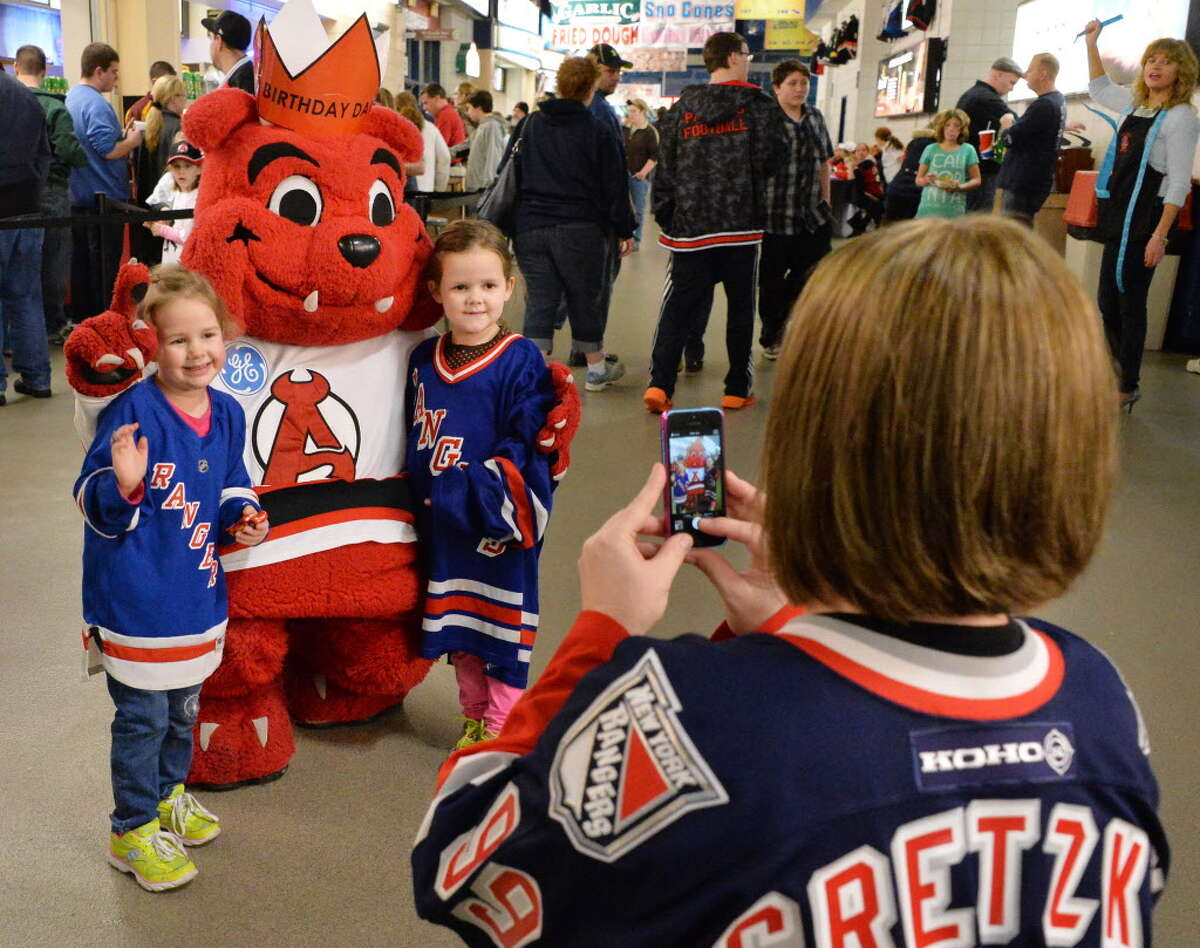 Daniella Richardson of Niskayuna takes a picture of daughters Molly, 3, left, and Chelsea, 5, with the Albany Devils mascot, Devil Dawg, before a game against the Manchester Monarchs at the Times Union Center on Jan. 11, 2014, in Albany, NY. (John Carl D'Annibale / Times Union archive)