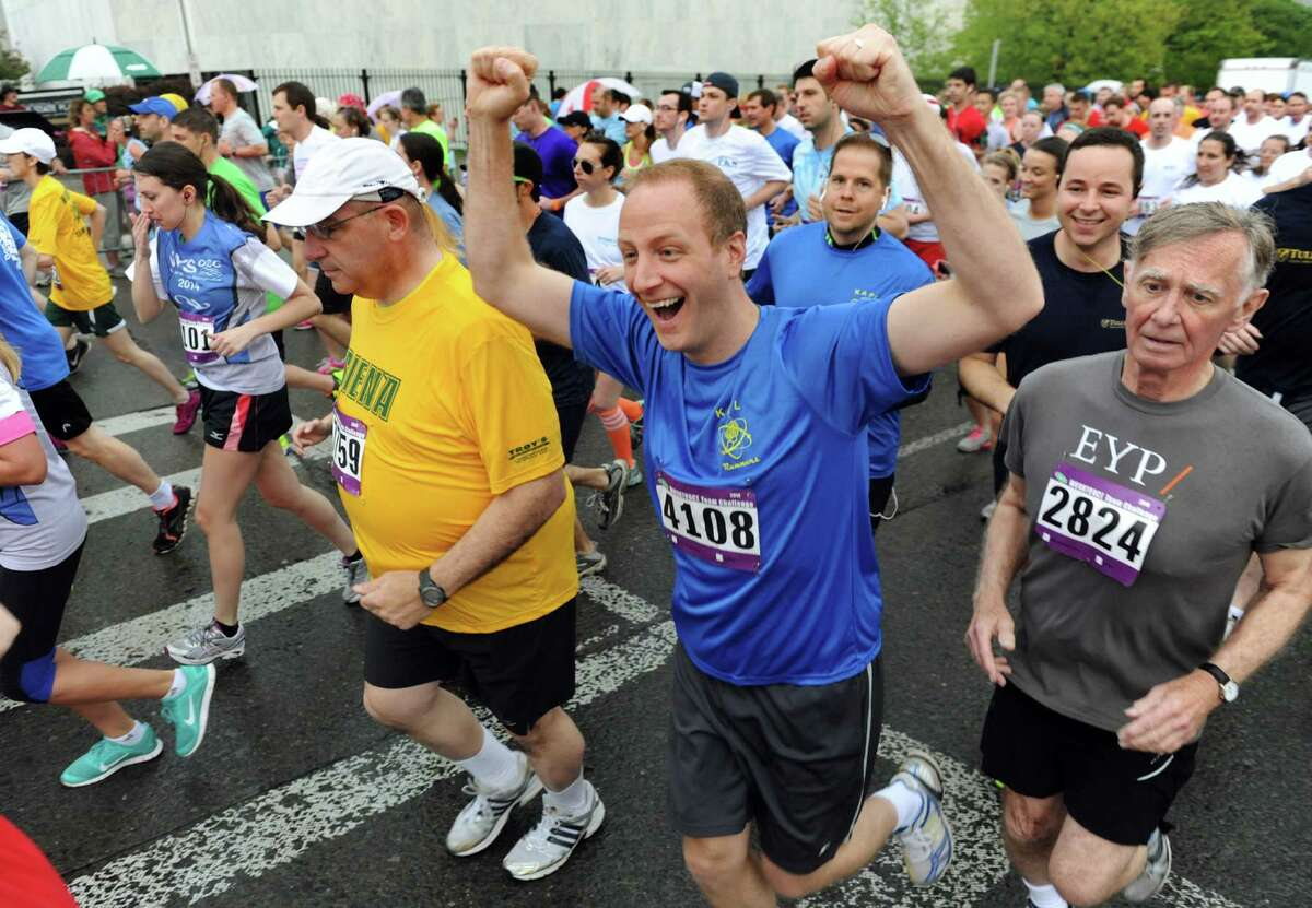 A runner celebrates the start of the 35th running of the CDPHP Workforce Team Challenge on Thursday, May 15, 2014, in Albany, N.Y. (Cindy Schultz / Times Union)