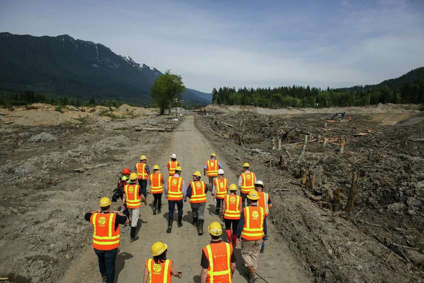 Officials walk into the debris field as Washington State Governor Jay Inslee checks on progress at the site of the Oso mudslide on Thursday, May 15, 2014 in Oso, Wash. Crews are progressing on unearthing State Highway 530. Some parts of the road will have to be rebuilt after it was washed away in the march mudslide that killed 41 people and left 2 missing.