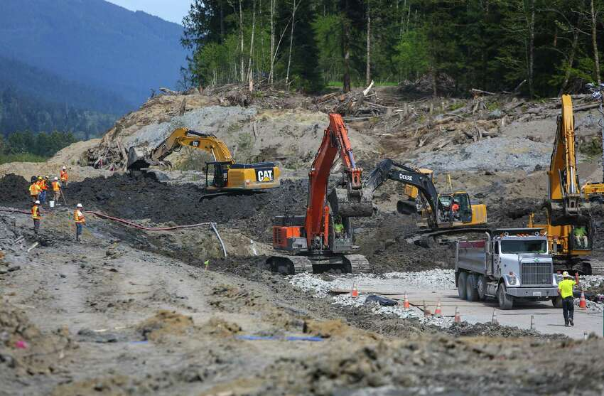 Work crews unearth State Highway 530 as Washington State Governor Jay Inslee checks on progress at the site of the Oso mudslide on Thursday, May 15, 2014 in Oso, Wash. Crews are progressing on unearthing State Highway 530. Some parts of the road will have to be rebuilt after it was washed away in the march mudslide that killed 41 people and left 2 missing.