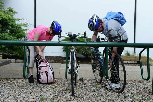 Cathleen Crowley, left, and Tim O'Brien, right, unlock their bikes and prepare to ride home from work Monday evening, May 12, 2014, at the Times Union in Colonie, N.Y. (Will Waldron/Times Union) Photo: WW / 00026868A