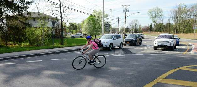 Cathleen Crowley navigates the roundabout at Albany Shaker and Maxwell Roads while riding home from work at the Times Union Monday evening, May 12, 2014, in Colonie, N.Y. (Will Waldron/Times Union) Photo: WW / 00026868A