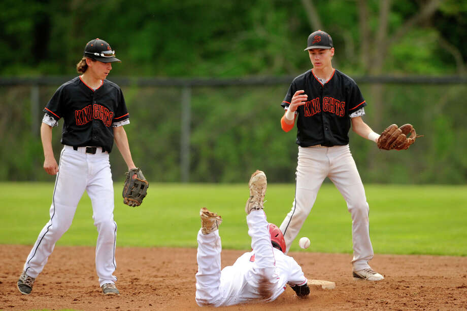 Stamford's Steve Browning, left, and Jay Devito look on as Greenwich's Sean Marks is hit with the ball while stealing second base during their baseball game at Greenwich High School in Greenwich, Conn., on Thursday, May 15, 2014. Greenwich won, 8-4. Photo: Jason Rearick / Stamford Advocate
