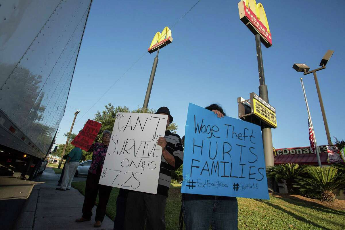 Irasema Cavazos, from the left, Hugo Aleman and Sandra Forester hold signs calling for a $15 minimum wage and the right of fast food workers to form a union as fast food workers and labor activists stage a protest outside the McDonald's in the 8600 block of Broadway, early Thursday, May 15, 2014 in San Antonio.