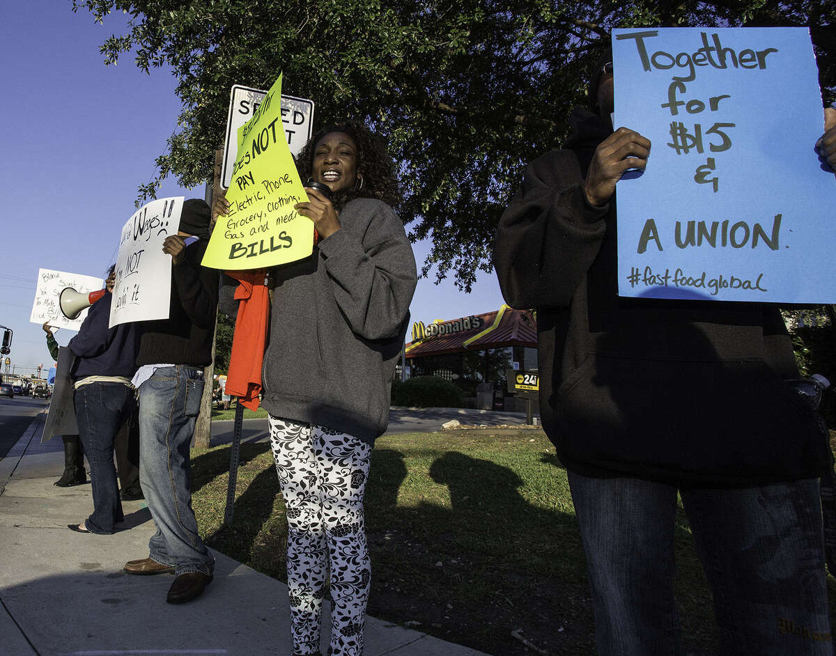 Lakiesha Harris (second from right) and Charles Richardson (right) hold signs calling for a $15 minimum wage and the right of fast-food workers to form a union as labor activists stage a protest outside the McDonald's. Harris works at Whataburger.