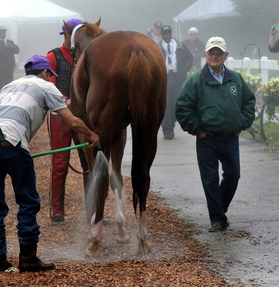 Trainer Art Sherman, right, watches as his Kentucky Derby winner California Chrome is bathed after his morning work Thursday May 15, 2014 at Pimlico Race Course in Baltimore, Maryland.      (Skip Dickstein / Times Union) Photo: SKIP DICKSTEIN