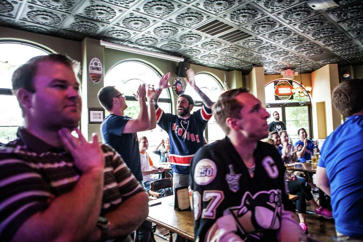 A goal by the New York Rangers elicits mixed reactions at the Maple Leaf Pub on Tuesday during their playoff game against the Pittsburgh Penguins.