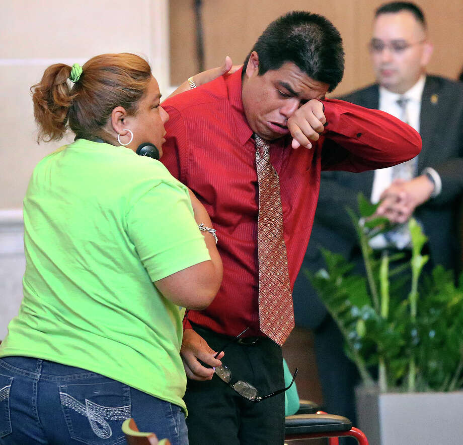 Christian Amador wipes away tears from his passionate plea before council as Adrianna Amador asked him to speak again as District 3 residents listen to city council vote on the rezoning of Mission Trails Mobile Home Park on May 15, 2014. Photo: TOM REEL, San Antonio Express-News