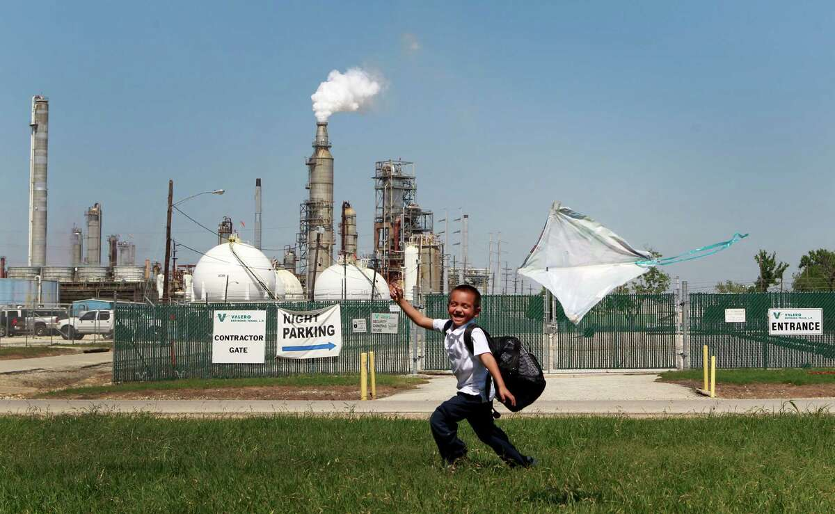 Joshua Martinez flies a kite Thursday in his aunt's yard on East Avenue P across from the Valero Houston Refinery. Revised federal environmental rules aim to clear the air the 6-year-old's kite soars through.