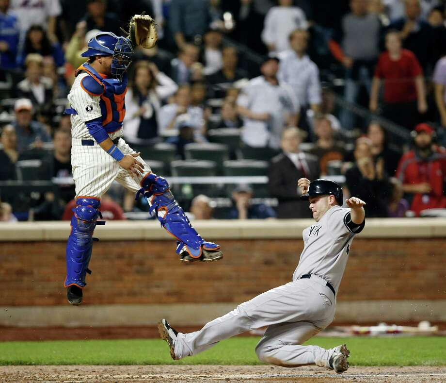 New York Yankees' Brian McCann scores on Alfonso Soriano's seventh-inning double, sliding in beneath a leaping New York Mets catcher Juan Centeno during a baseball game in New York, Thursday, May 15, 2014. (AP Photo/Kathy Willens) ORG XMIT: NYM117 Photo: Kathy Willens / AP