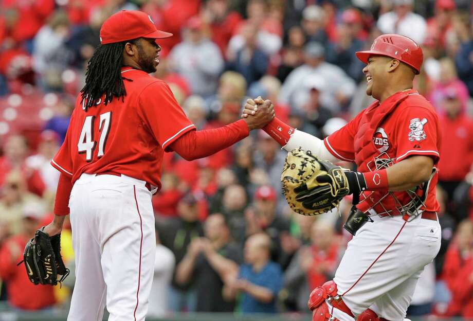 Reds catcher Brayan Pena congratulates Johnny Cueto, left, after a three-hitter against the Padres in the first game of a doubleheader. Cueto lowered the majors' best ERA to 1.25 with his third complete game this year. Photo: Al Behrman, STF / AP