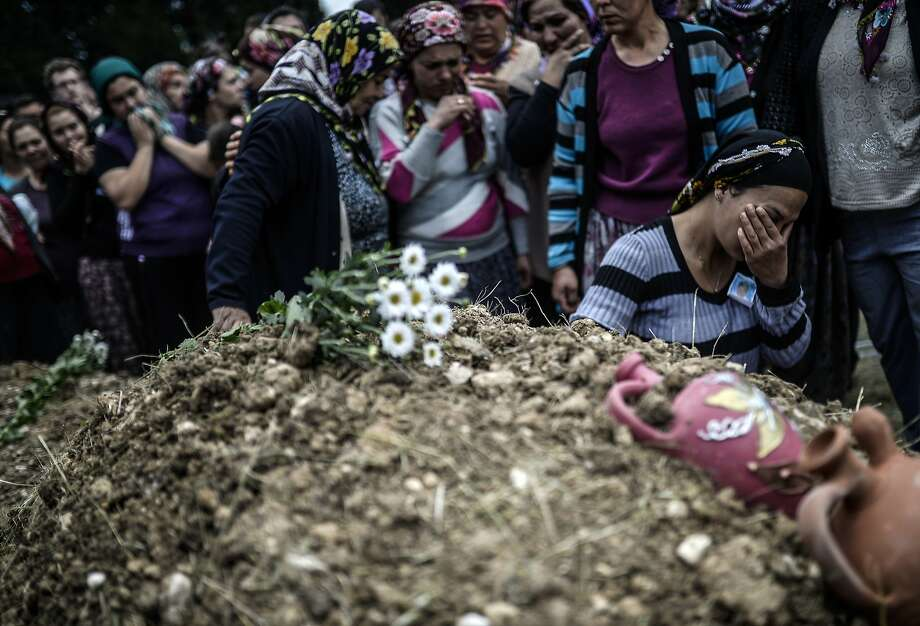TOPSHOTS Duygu Colak, reacts as she sits in front of her husband Ugur's grave during a funeral ceremony in the western town of Soma in the Manisa province on May 15, 2014. Turkey's four biggest unions will hold a one-day protest strike as anger over the country's worst mining accident mounts, with 282 workers confirmed dead and scores still trapped underground. AFP PHOTO/BULENT KILICBULENT KILIC/AFP/Getty Images Photo: Bulent Kilic, AFP/Getty Images