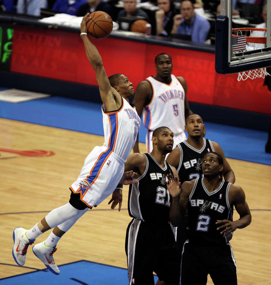 Oklahoma City Thunder's Russell Westbrook (0) dunks over San Antonio Spurs' Tim Duncan (21) and San Antonio Spurs' Kawhi Leonard (2) during the first half of game six of the NBA Western Conference Finals in Oklahoma City, Okla. on Wednesday, June 6, 2012. Photo: Kevin Martin, San Antonio Express-News / © 2012 San Antonio Express-News