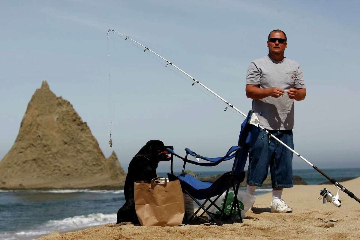 Bill White of Daly City fishes with his dog Bella at Martins Beach in San Mateo County in May.