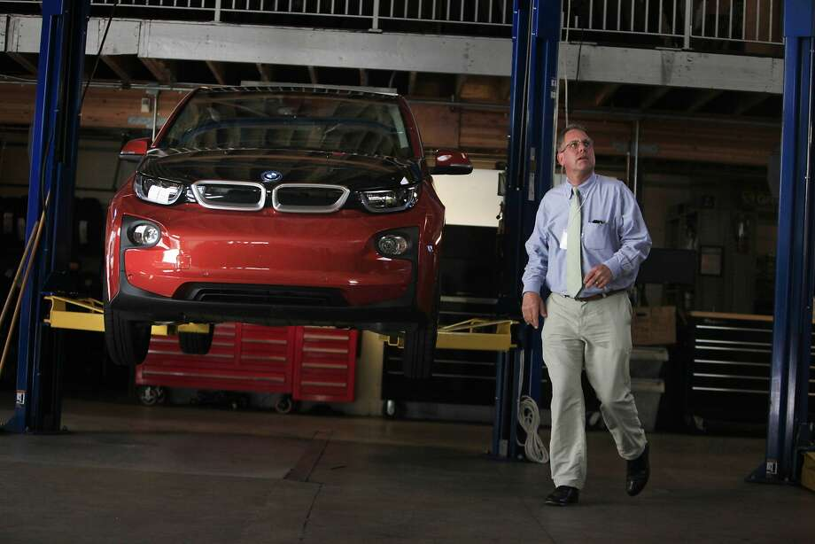 John Goodwin of the Metropolitan Transportation Commission passes a BMW i3 at an event promoting electric cars. Photo: Lea Suzuki, The Chronicle